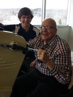 Young student working with elderly man